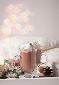 冬の早朝、ベッドの上の白いトレイにココアを2杯