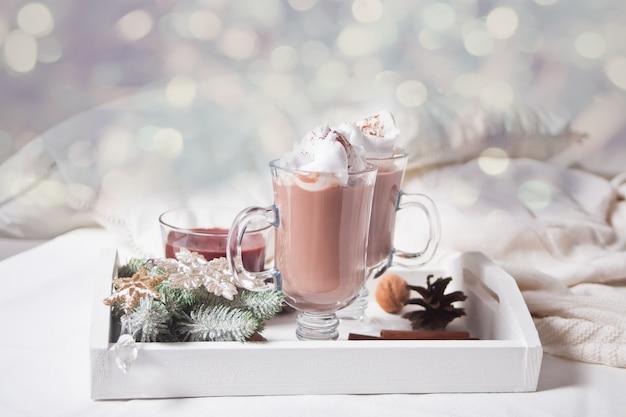 冬の早朝のベッドの上のココアホワイトトレイを2杯