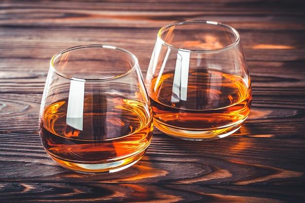 ダークブラウンの木製テーブルにウイスキー2杯