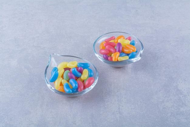 青灰色の表面にフルーツスウィートビーンキャンディーが付いた2枚のガラスプレート