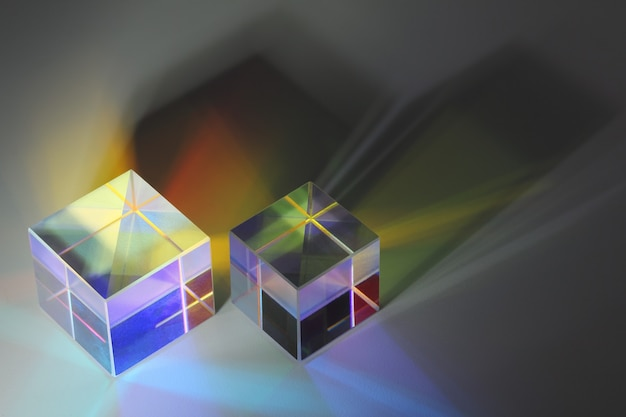 Two glass prism cubes closeup refract light and cast colored shadows