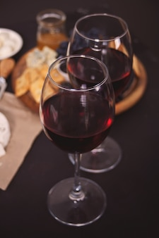 Two glass of red wine and plate with assorted cheese, fruit and other snacks for party