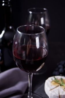 Two glass of red wine and plate with cheese