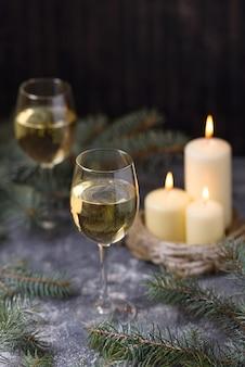 2つのグラスワインとクリスマスツリーのキャンドル