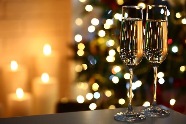 Два бокала с шампанским на столе на елке и фоне камина