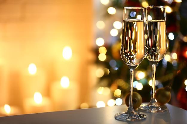Два бокала шампанского с конфетами и шарами на столе на фоне елки и камина