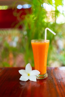 Two glass with freshly squeezed juice and frangipani flower