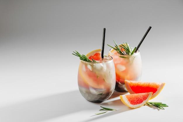 Два бокала с коктейлем из грейпфрута и розмарина. летние напитки со свежими цитрусовыми и льдом.