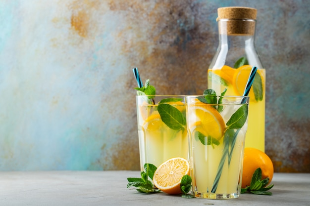 Two glass with lemonade or mojito cocktail with lemon and mint, cold refreshing drink or beverage