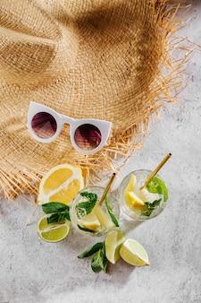 Два стакана с лимонадом или коктейлем мохито. летние напитки со свежими цитрусовыми и льдом.