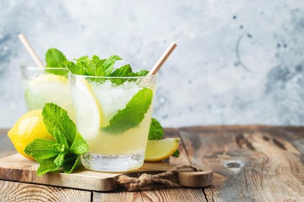 Два стакана лимонада или коктейля мохито с лимоном и мятой, холодный освежающий напиток или напиток со льдом на деревенском синем фоне. скопируйте пространство.