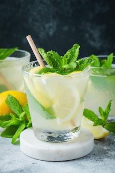 Два стакана лимонада или коктейля мохито с лимоном и мятой, холодный освежающий напиток или напиток со льдом на деревенском синем фоне.