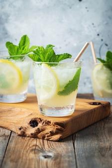 Два стакана лимонада или коктейль мохито с лимоном.
