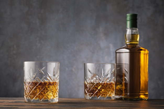 Two glass with whiskey and alcohol bottle