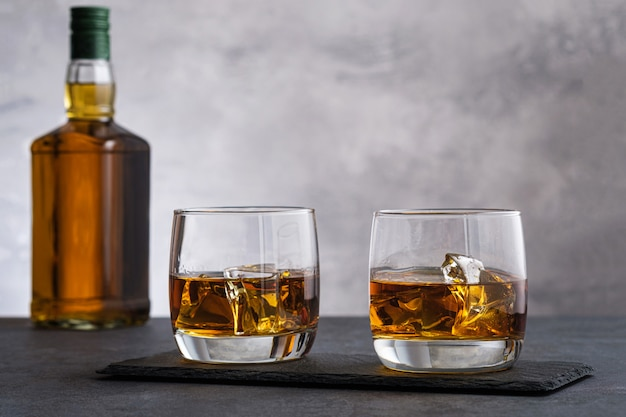 Two glass with whiskey and ice cubes on wall bottle