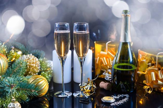 クリスマスや新年のロマンチックなお祝いのために、ヴィンテージ時計の横にある装飾的な松の枝、キャンドル、金のつまらないもの、ギフトボックスに囲まれたグラス2杯とシャンパンのオープンボトル