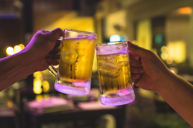 Two glasses of beer cheers together between friend in the low light bar and restaurant