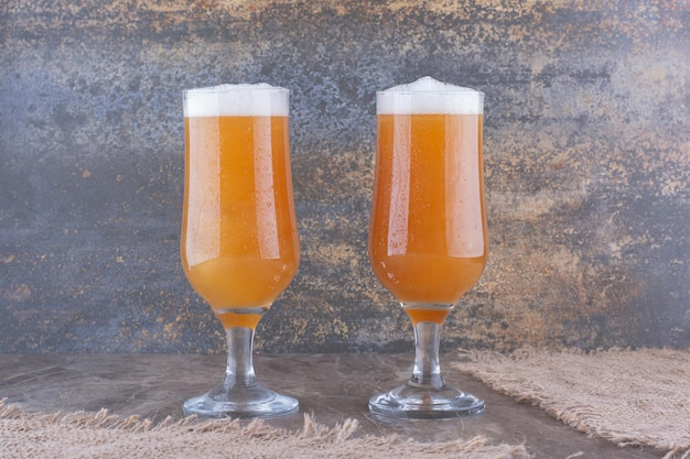 Two glasses of beer on marble table. high quality photo
