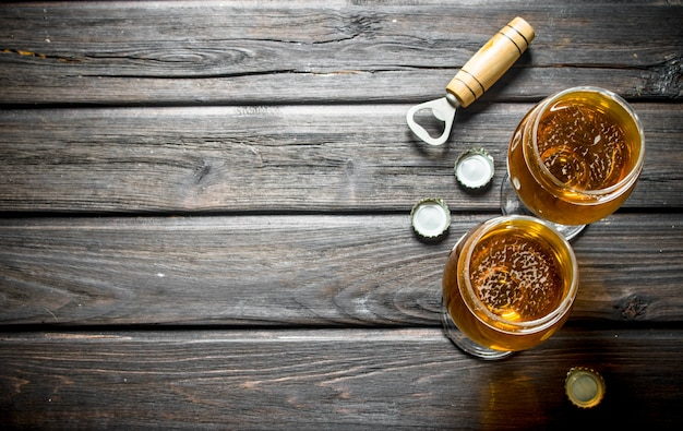 Two glasses of beer, opener and lcovers. on wooden background