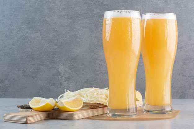 Due bicchieri di birra con formaggio e limone a fette su grigio.