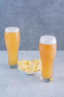 Due bicchieri di birra con patatine fritte sulla superficie grigia