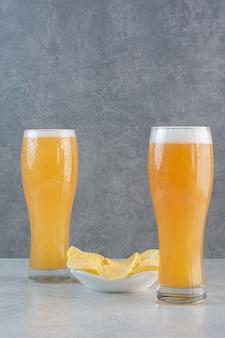 Due bicchieri di birra con patatine fritte su grigio.