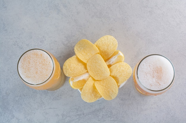 Two glasses of beer with potato chips on gray. Free Photo