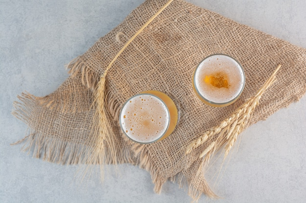 Two glasses of beer with wheat on sackcloth .