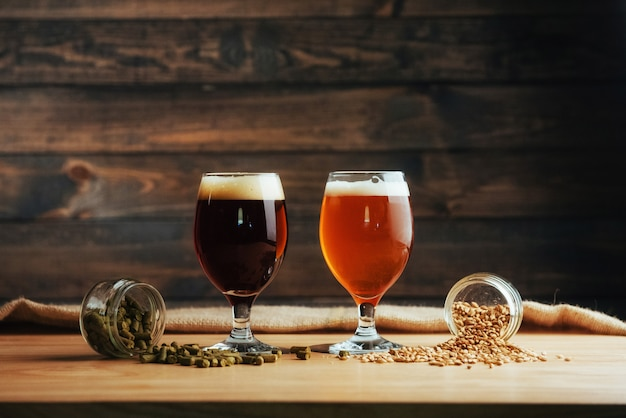 Two glasses of beer on a wooden table grains