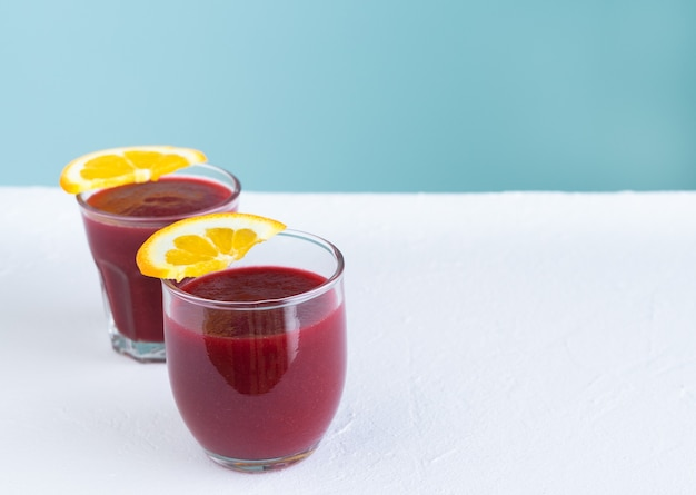 Two glasses of beet juice on white and blue background with orange slices decoration. copy space.