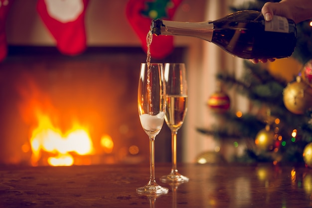 Two glasses being filled with champagne on table next to christmas tree and burning fireplace