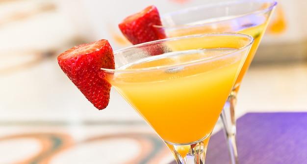 Two glasses of bellini cocktail with prosecco, strawberry decor, italian bar