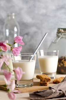 Two glasses and a bottle of milk cereal bars some nuts and raisins in a jar with pink flowers