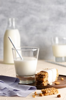 Two glasses and a bottle of milk and cereal bars with a light blue napkin