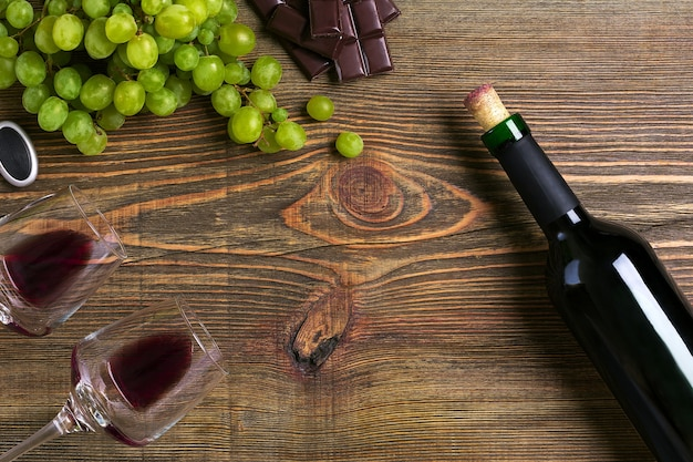 木製のテーブルにグラス2杯、赤ワインとブドウのボトル。上面図。スペースをコピーします。フラットレイ。静物