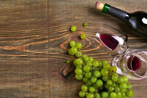 Два бокала, бутылка красного вина и винограда на деревянном столе