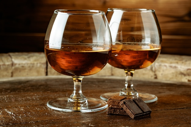 Two glasses of bourbon or scotch, or brandy and pieces of dark chocolate
