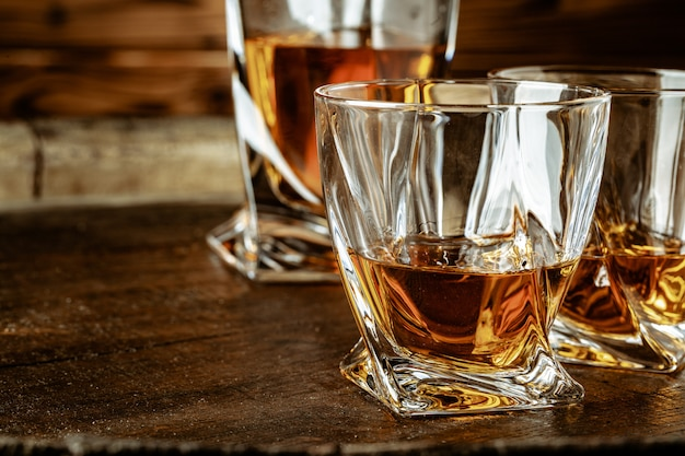 Two glasses of brandy or cognac and bottle on the wooden table