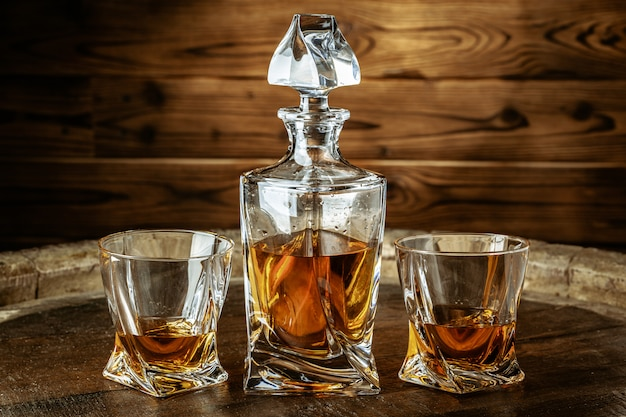 Two glasses of brandy or cognac and bottle on wooden table