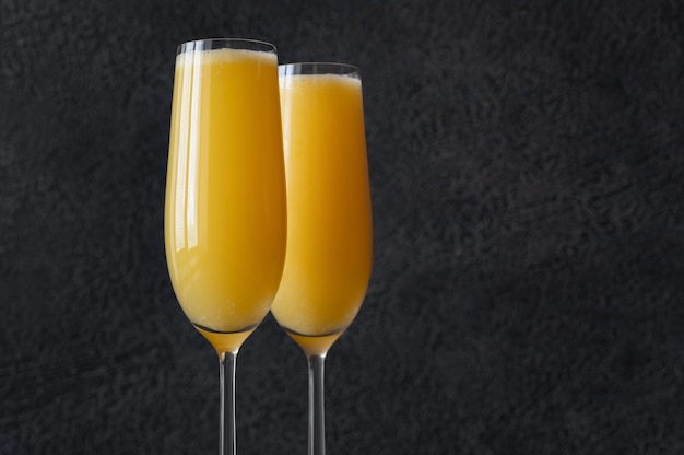 Two glasses of buck's fizz cocktail on black background