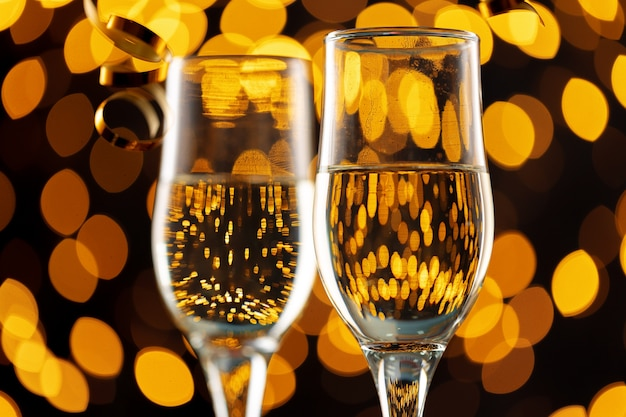 Two glasses of champagne against bokeh lights