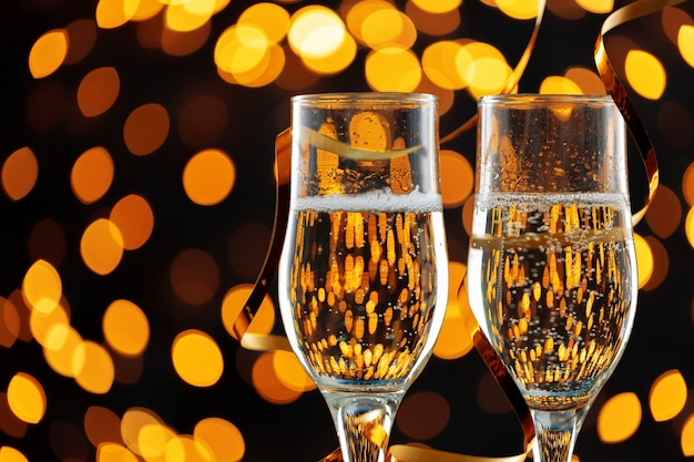 Two glasses of champagne against shiny bokeh lights background