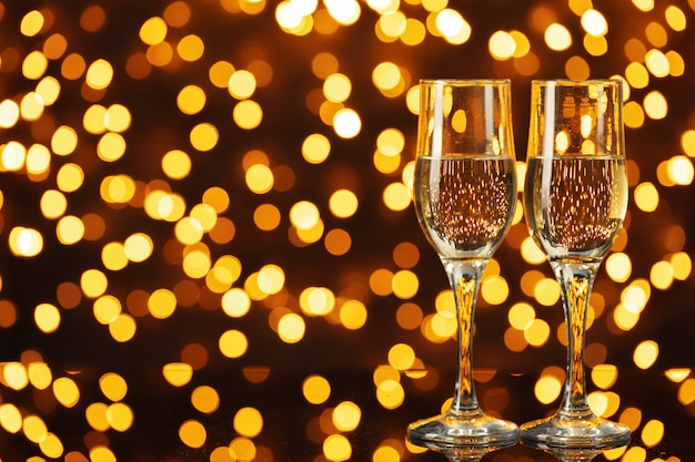 Two glasses of champagne against shiny bokeh lights