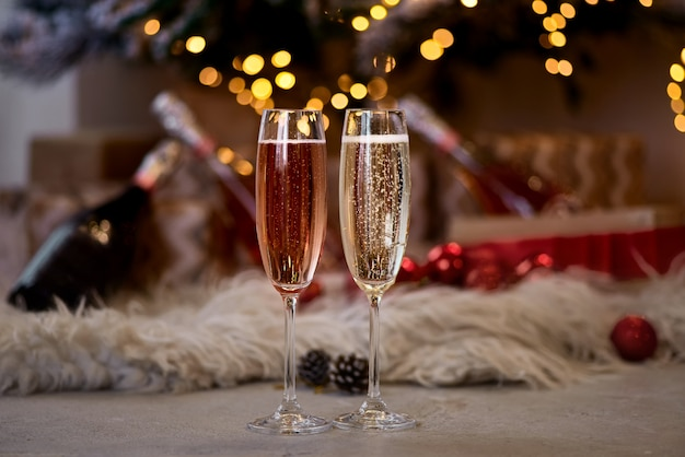 Two glasses of champagne are standing near the tree