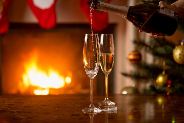 Two glasses of champagne being filled from bottle. christmas tree and burning fireplace on the background