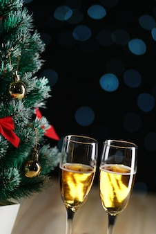 Two glasses of champagne beside small christmas tree dark glow lights background. copy space