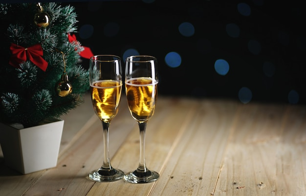 Two glasses of champagne beside small christmas tree dark glow lights background. room for text