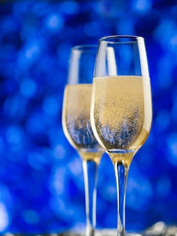 Two glasses of champagne on a blue background. merry christmas and happy new year