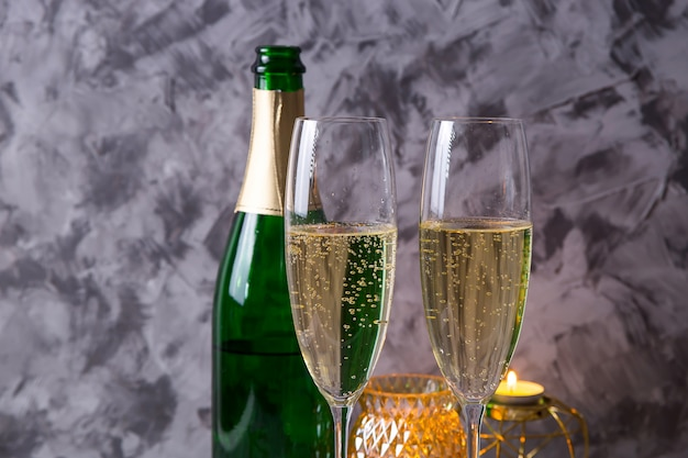 Two glasses of champagne next to a bottle