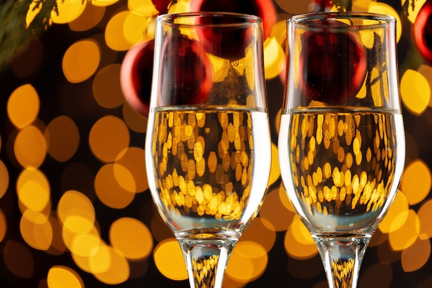 Two glasses of champagne and christmas baubles on shiny bokeh lights background